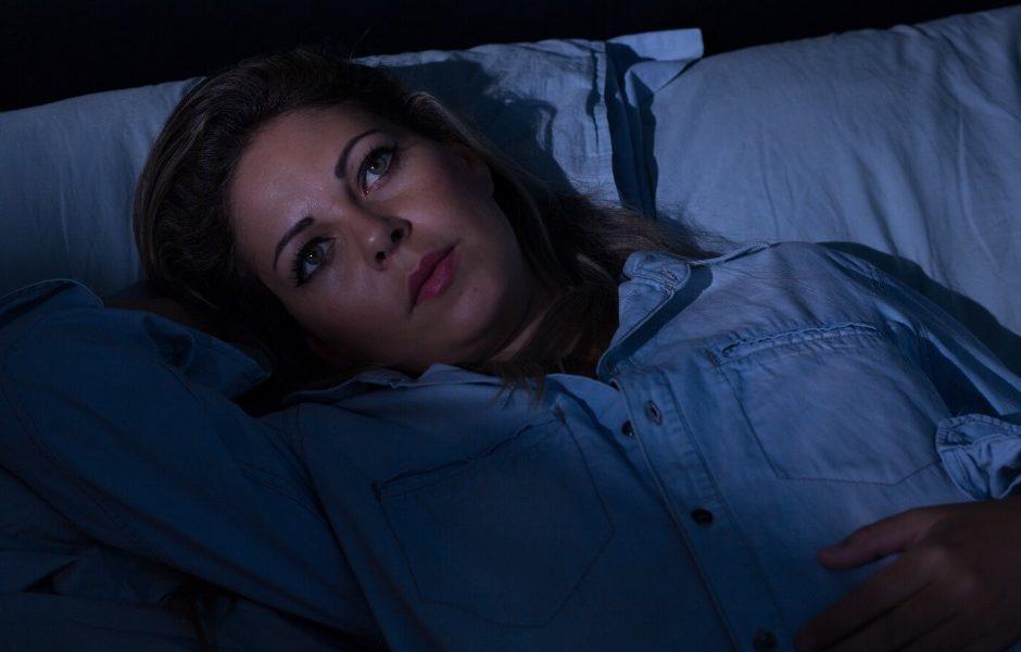 Frau liegt schlaflos im Bett, da sie Angst hat schwer krank zu sein